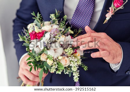 the groom holding cotton wedding bouquet of flowers