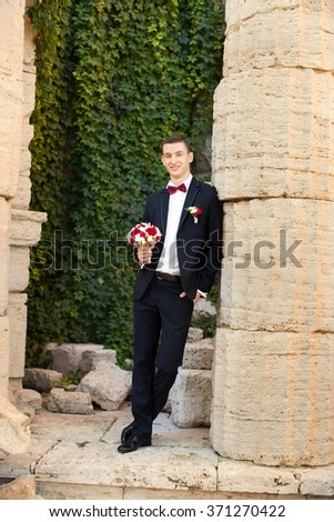 The groom holds a tie and smiles.Portrait of the groom in the park on their wedding day.Rich groom on their wedding day