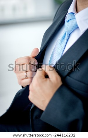 The groom holds jacket