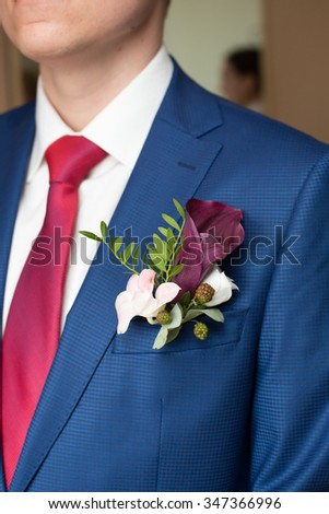 the groom in a blue suit and a claret buttonhole