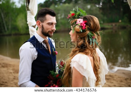 the groom in a wedding suit and boutonniere and bride in lace dress with bouquet and wreath , wedding arch on a background of lake - stock photo