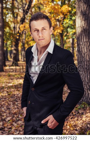 The groom in black suit outdoors is standing in autumn park. Male portrait.  - stock photo