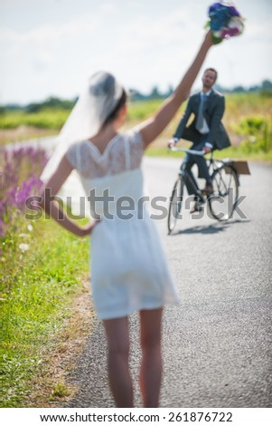 The groom is coming back for his bride on a bike. Beautiful couple having fun for their honeymoon - stock photo
