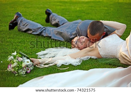 The groom kisses the bride lying on a grass in park - stock photo