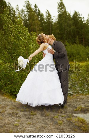 The groom passionately kisses the bride among a grass and trees - stock photo