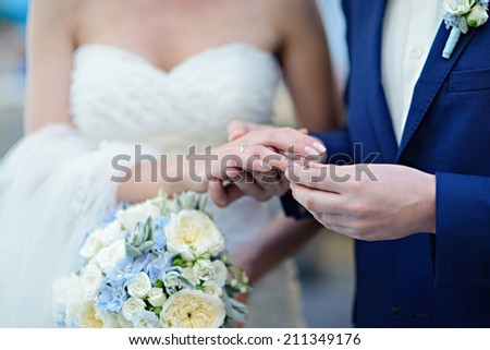the groom puts the ring on the bride - stock photo