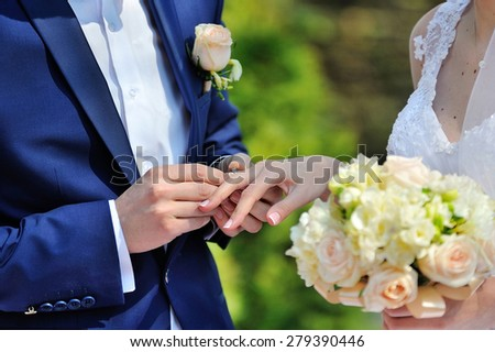 The groom puts the ring on the bride's finger - stock photo