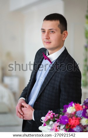 The groom stands leaning near colors - stock photo
