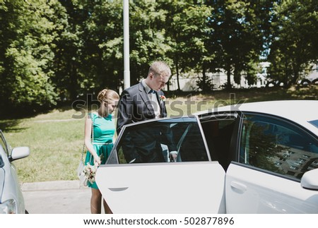 The groom stands near car