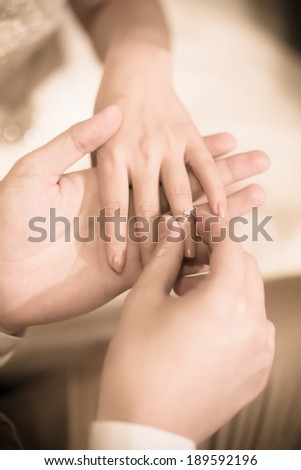 The groom wearing wedding ring for his bride - stock photo