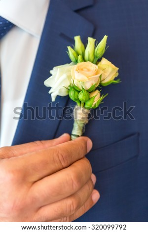 The groom wears boutonniere of roses on his blue jacket before the wedding ceremony , vertical photo