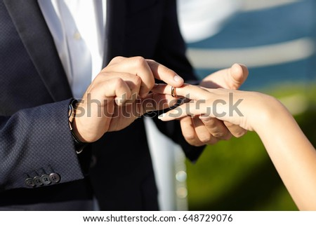 The groom wears gold ring in the bride's finger during the ceremony
