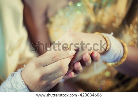 The groom wore a ring to the bride at the wedding.Wedding in Thailand  - vintage filter. - stock photo