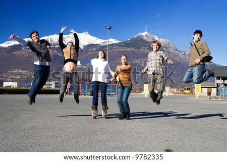 The group of jumping people on a background of mountains