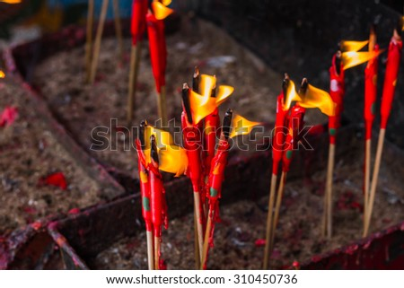 The group of red candle in matal incense base  abstract blur dark background - stock photo