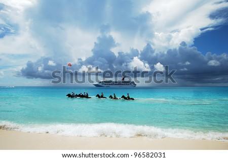 The group of tourists riding horses in Caribbean sea on Half Moon Cay, The Bahamas. - stock photo