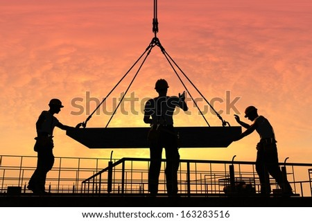 The group of workers working at a construction site. - stock photo