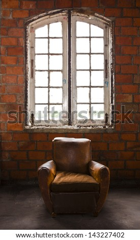 The grunge old armchair with top hi-light over the large window - stock photo