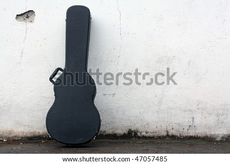 The guitar case rest on a wall. - stock photo