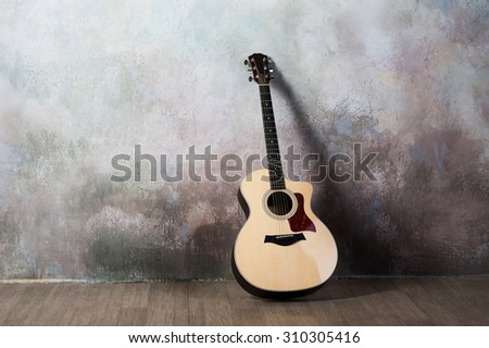 The guitar stands near the wall in the style of grunge, music, musician, hobby, lifestyle, hobby - stock photo