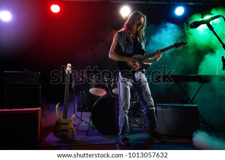 The guitarist performs on stage. Stage light, smoke.