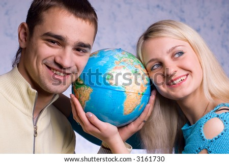 The guy and the girl hold the globe on a blue background