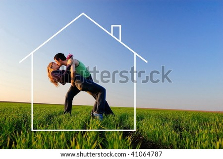 The guy and the girl kiss in a autumn field and dreams about the new house - stock photo
