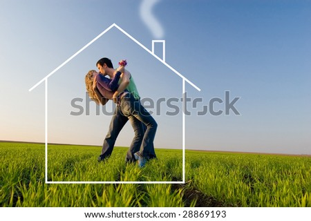 The guy and the girl kiss in a spring field and dreams about the new house - stock photo
