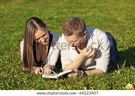 The guy and the girl lie in park on a grass with the book