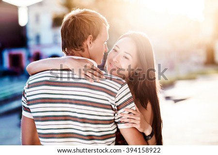 The guy embraces his girlfriend during a walk in the fresh air - stock photo