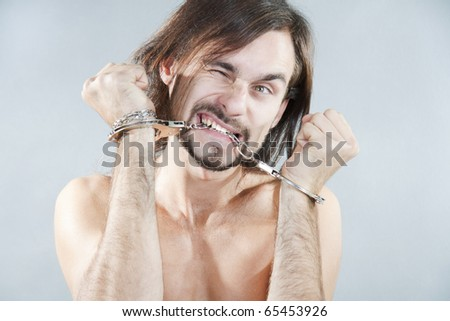 The guy gnaws his handcuffs - stock photo