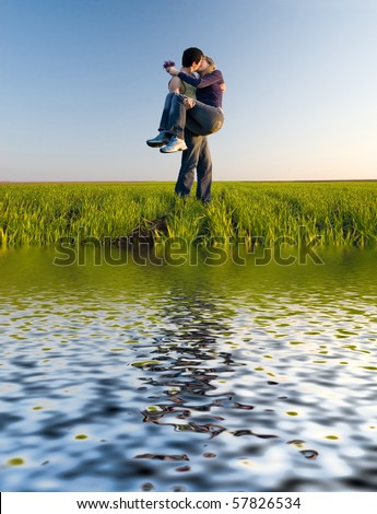 The guy holds the girl on hands and kisses - stock photo
