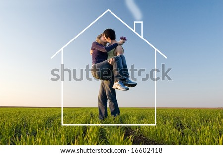 The guy holds the girl on hands, kisses and dreams about the new house - stock photo