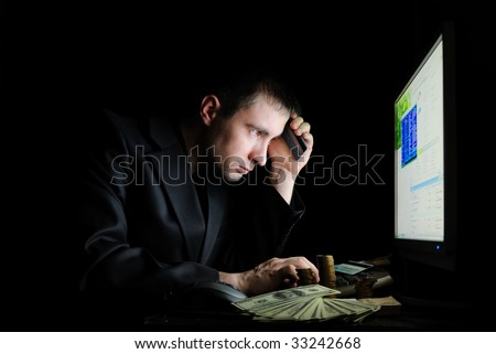 The guy in a jacket with money working on pc - stock photo