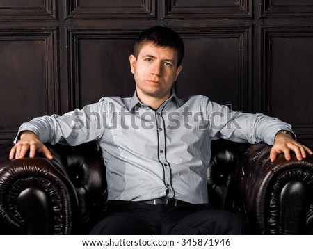 The guy in a shirt sitting in a chair in front of the English walls of wooden panels