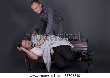 The guy in the suit covers sleeping on a bench guy cloak - stock photo