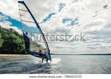 the guy in the waggon swims on the windsurf on the lake
