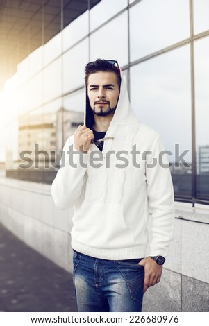 the guy in the white sweater outdoors. - stock photo