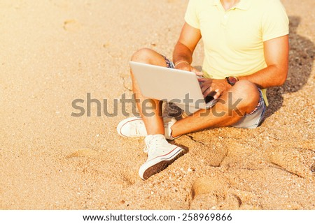 The guy in the yellow T-shirt and shorts sits on a sandy beach and working on laptop - stock photo