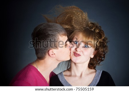 The guy kisses the young woman. The young woman playfully was surprised - stock photo