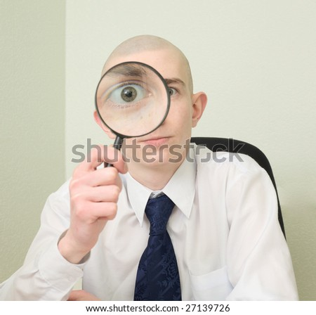 The guy looks through the big magnifier - stock photo