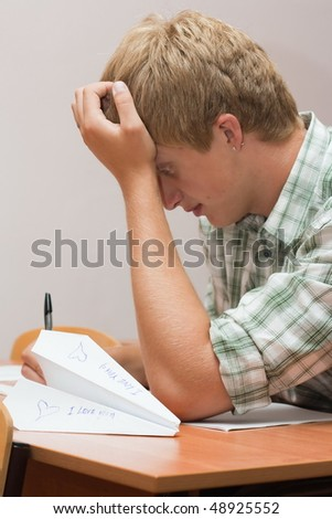 The guy prepares for examination, on a table the paper plane with the love message lies - stock photo