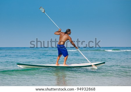 The guy with an oar on a surfboard (Stand Up Paddling). The beautiful brawny guy with an oar in hands on a surfboard. - stock photo