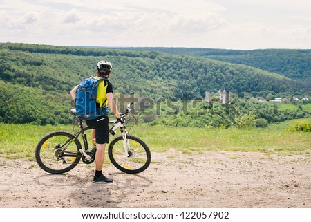 The guy with the blue backpack riding a bicycle and looking the ruins of the old castle - stock photo