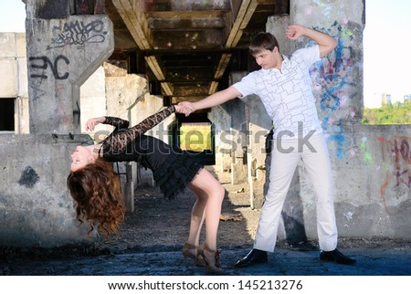 The guy with the girl dance a tango in abandoned room - stock photo