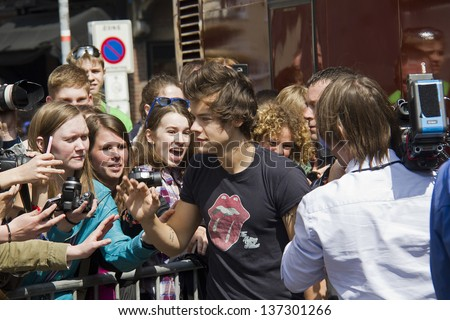 THE HAGUE, HOLLAND - MAY 3: Harry Styles of the boy band One Direction leaves Hotel des Indes among a crowd of teenage fans in The Hague, Holland on May 3, 2013 - stock photo