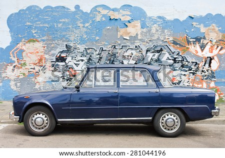 THE HAGUE-JULY 17, 2009. Alfa Romeo Giulia in front of facade with graffiti. Alfa Romeo Giulia (105 series) is a sports saloon produced from 1962 to 1978 with powerful engine in light-weight chassis. - stock photo