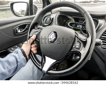 THE HAGUE, NETHERLANDS - APR 22, 2015: Driver using cruise control at steering wheel while driving a car - stock photo