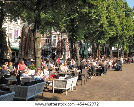 The Hague, Netherlands - July 8, 2016:  Patrons frequenting cafes and restaurants at the historic city square called  The Plain in The Hague in the afternoon on a sunny spring day.