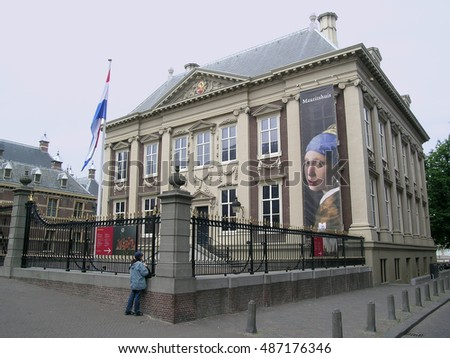 THE HAGUE, NETHERLANDS - JULY 4, 2008: The Mauritshuis art museum, which contains works by Vermeer (his Girl with a Pearl Earring on the poster on the facade), Rembrandt and others.